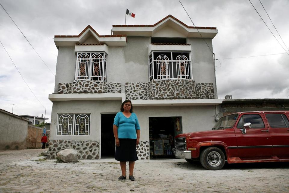 A woman in front of her home in a Mexican village, built with money her 18-year-old son sent home from the United States.