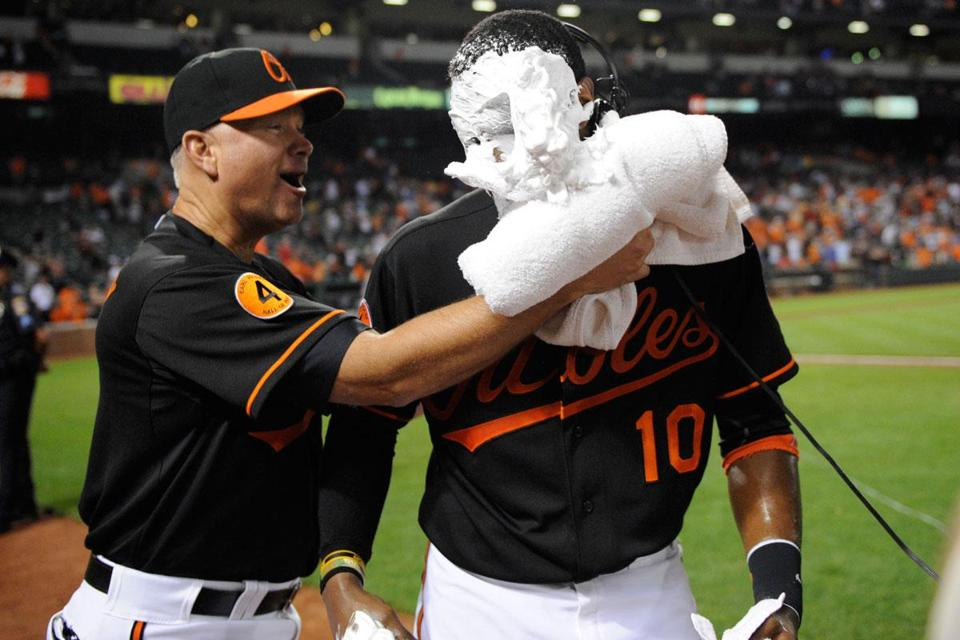 Adam Jones, who hit two homers Friday, gets a postgame shaving-cream pie from Orioles hitting coach Jim Presley.