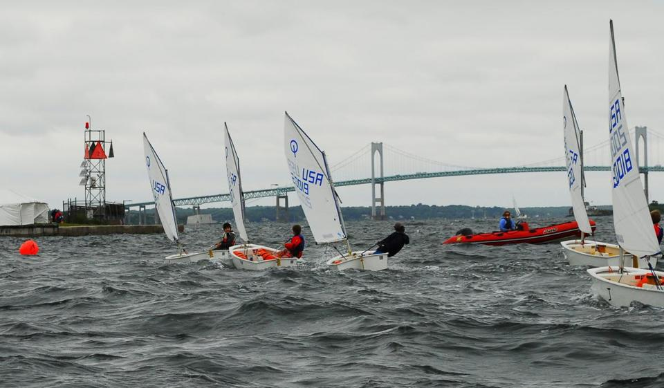 Groups of young sailors try their racing skills in Newport Harbor as part of their Sail Newport instruction.  In the background is the Claiborne Pell Bridge spanning the East Passage of Narragansett Bay.