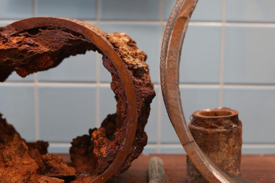 A cross-section of an older pipe (left) is displayed alongside a newer pipe, showing the deposits that can accumulate over time.