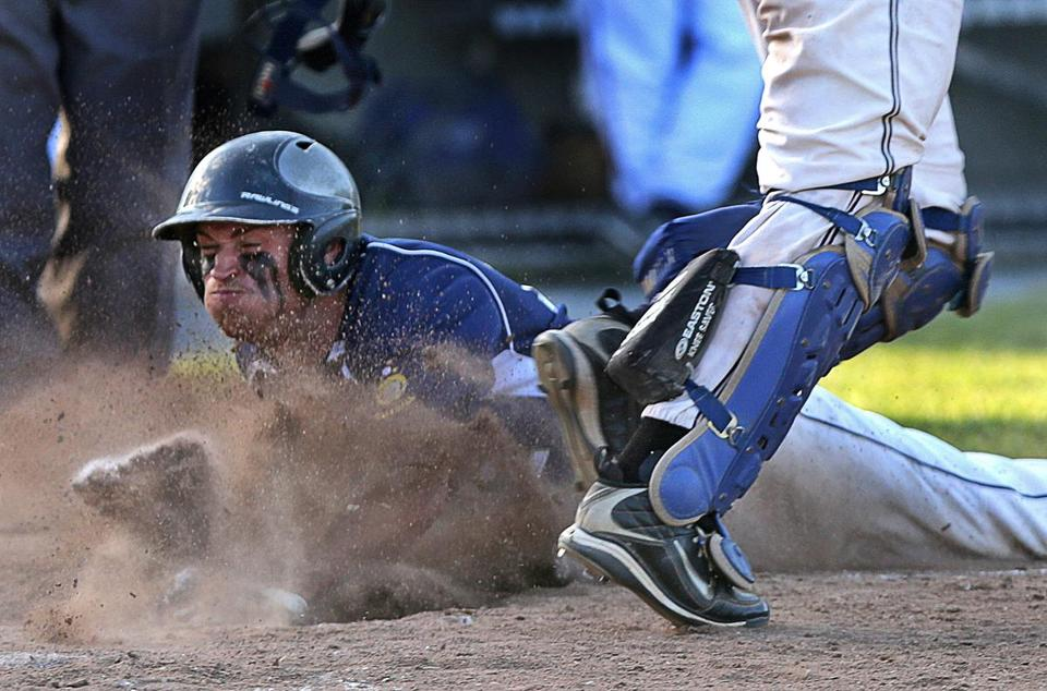 Lowell's Mike Hart (12) slides safely into home in the fourth inning against Norwood during the state Legion tourney.