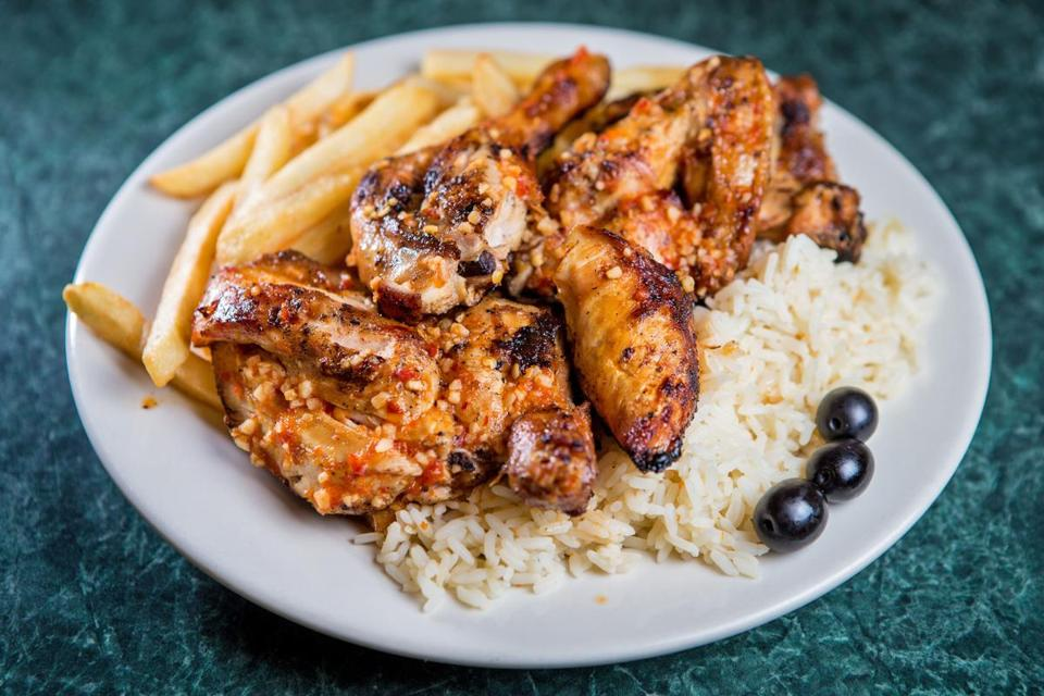 """½ frango no churrasco,"" a half rotisserie barbecue chicken with fries and rice pilaf at J & J Restaurant & Takeout."