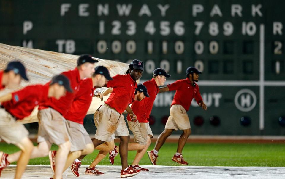 The grounds crew removed the tarp after a brief rain storm during a game against the Tampa Bay Rays inning at Fenway Park.