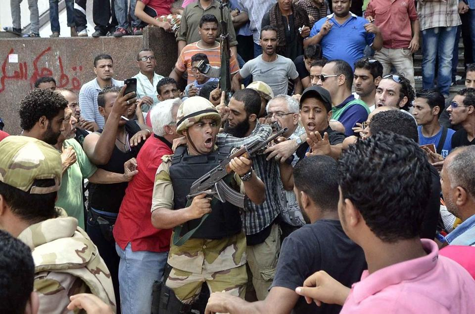 An army officer pointed his weapon at the crowd Saturday as he helped an Islamist man leave Cairo's Fath mosque where supporters of ousted president Morsi were holed up. Security forces were trying to convince the supporters to leave.