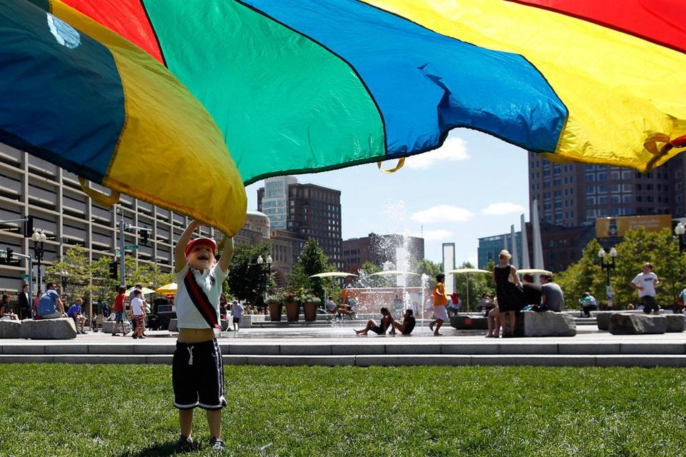 Sam Lottner played with a rainbow-colored parachute on the Rose Fitzgerald Kennedy Greenway in Boston.