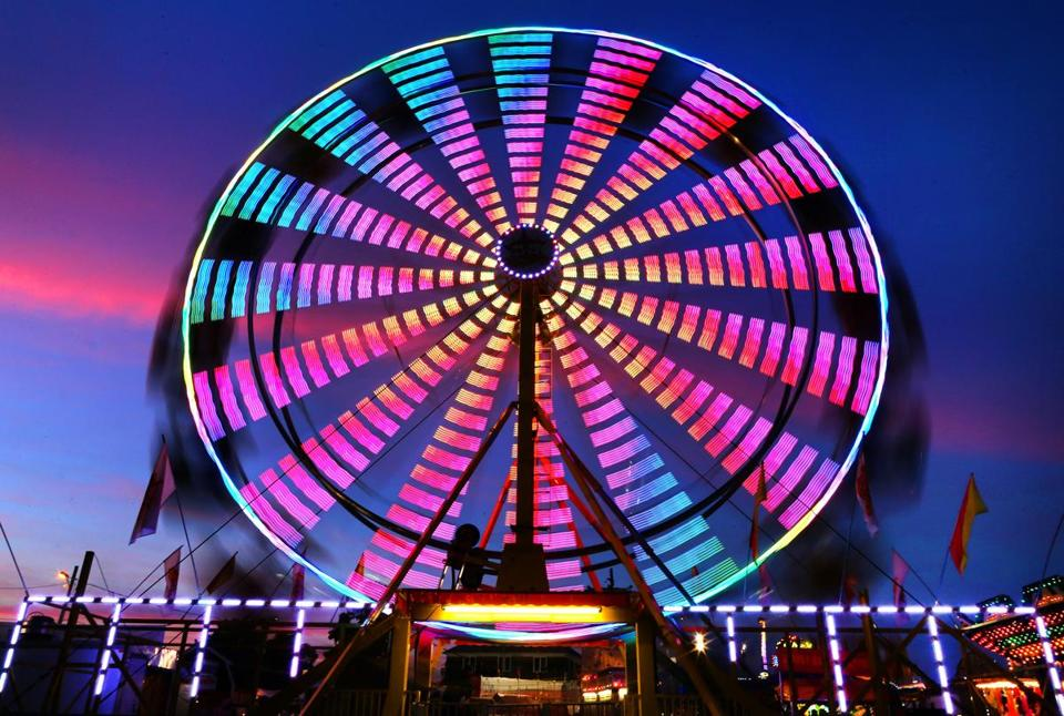An old favorite, the ferris wheel, lights up the sky as dusk falls on the Marshfield Fair, which runs through Sunday.