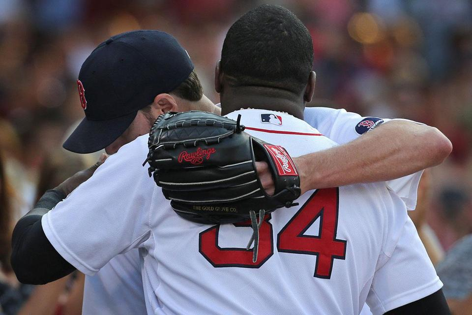 After leaving the game in the seventh, Sox starter John Lackey gets a hug from David Ortiz as he returns to the dugout.