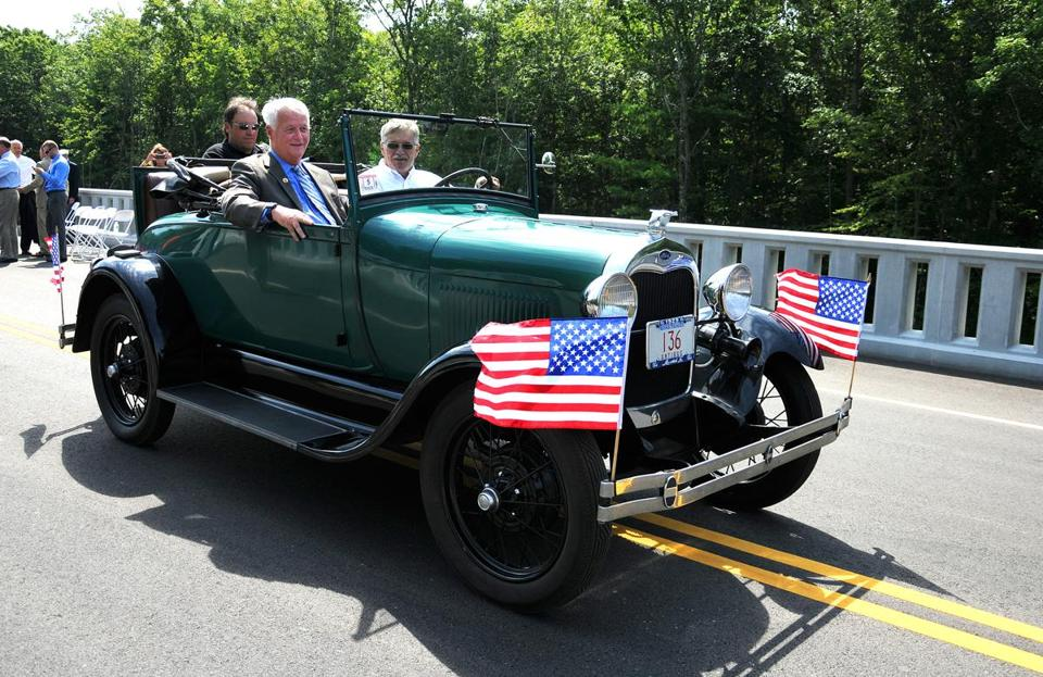 Former US representative William Delahunt (left) was driven in a 1929 Model A Ford by Ron Lum along the newly dedicated Bill Delahunt Parkway at SouthField on Monday.