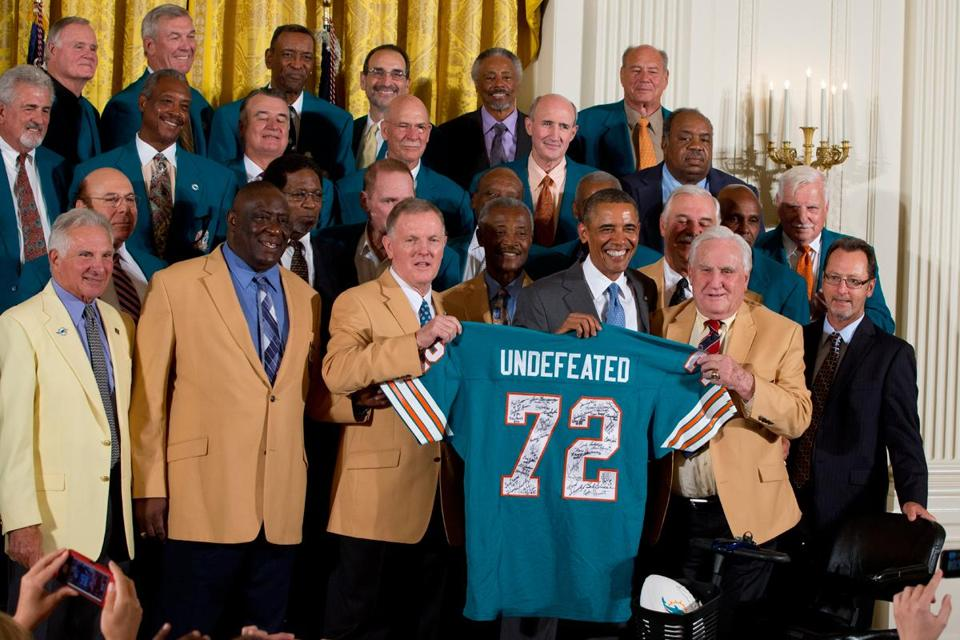 Barack Obama holds a jersey presented by quarterback Bob Griese (left), coach Don Shula, and members of the Super Bowl VII champions.