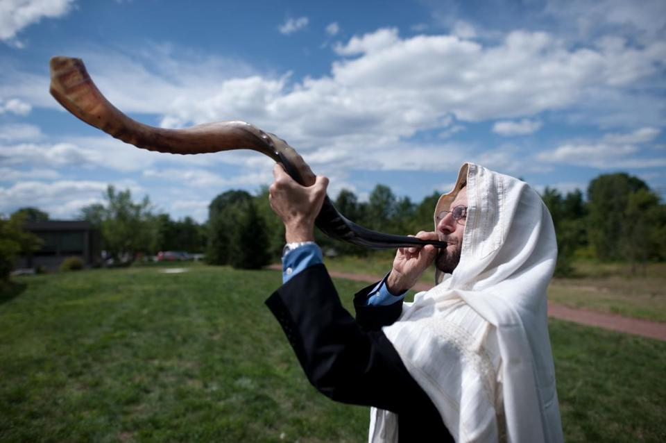 "Rabbi Darby Leigh, who is deaf, practiced blowing the ceremonial shofar outside Concord's Congregation Kerem Shalom. ""I prefer the lower bassy sound,'' he says. ""I can feel it better."""