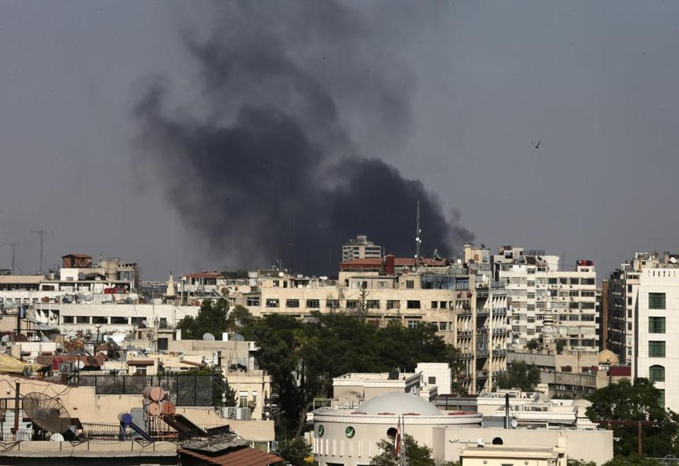 Smoke rises amid shelling in Damascus on Sunday. Syria said it made a deal for UN experts to test for toxic nerve agents.