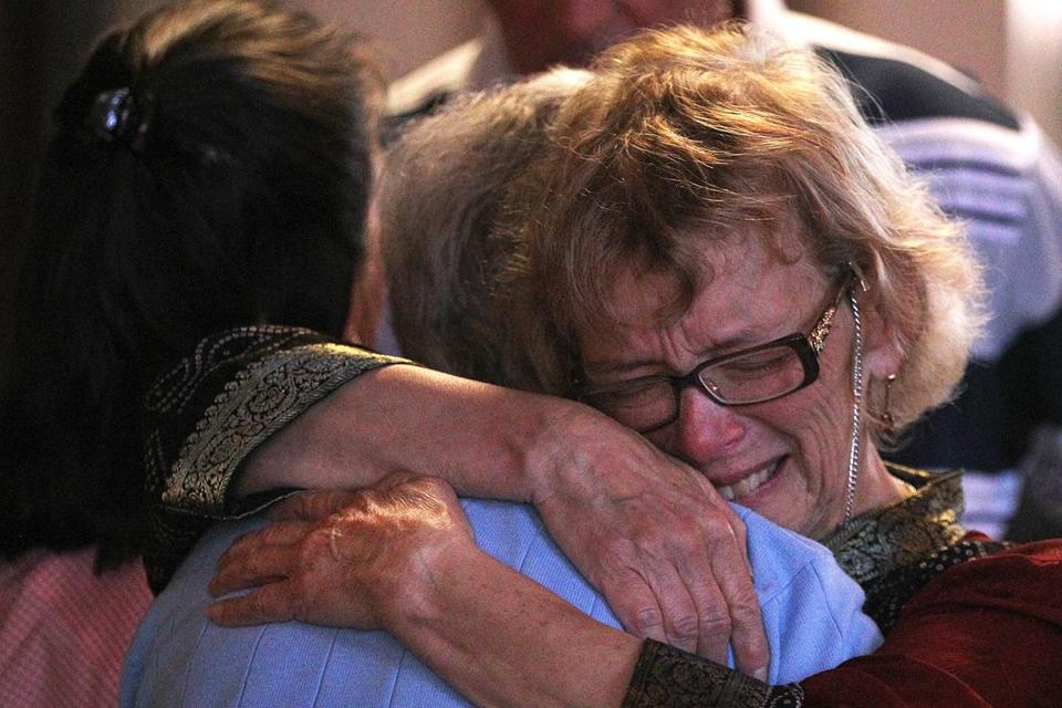 Dianne Scollard (right), wife of St. John pastor John Scollard, embraced church member Marina Tamburi on Sunday.