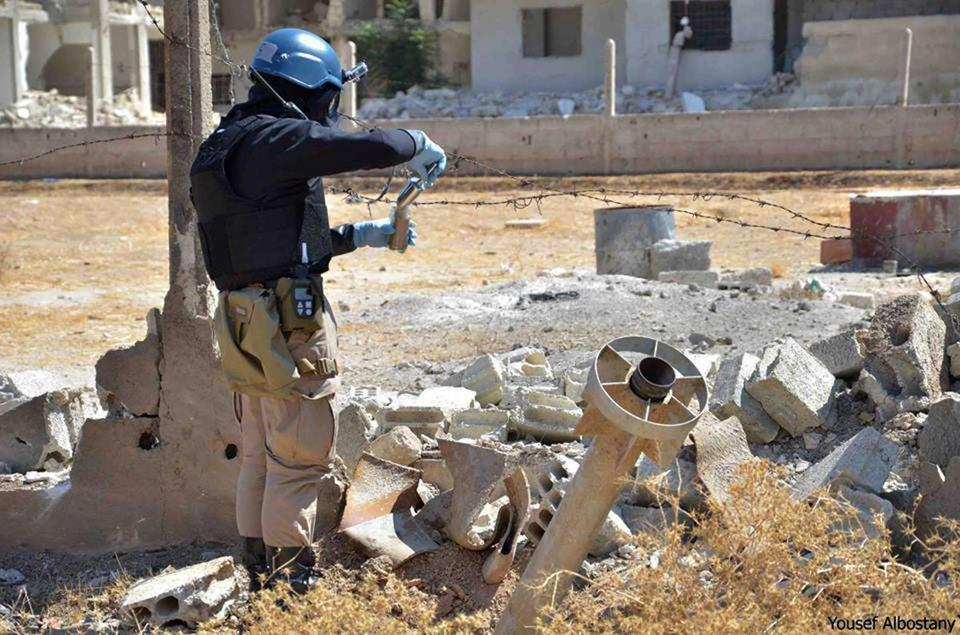 A member of a UN investigation team took samples of sand near a part of a missile outside Damascus on Wednesday.