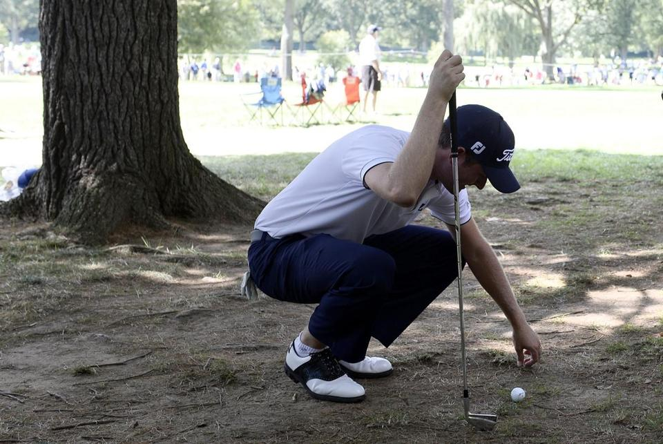 Webb Simpson clears debris from around his ball so he can have a clean approach.