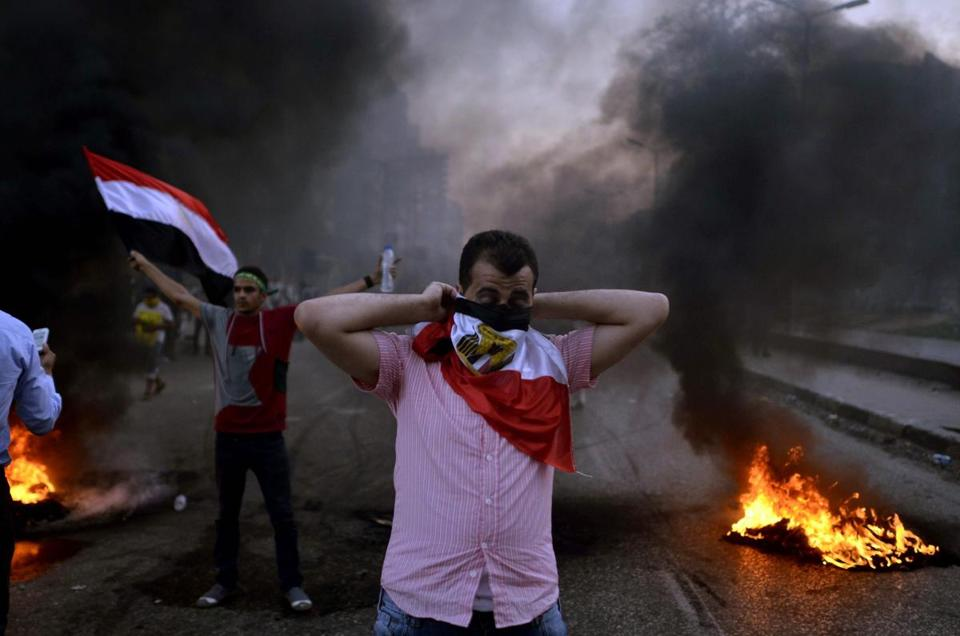 A protester covered his face with a flag as Muslim Brotherhood supporters and security forces clashed in Cairo Friday.