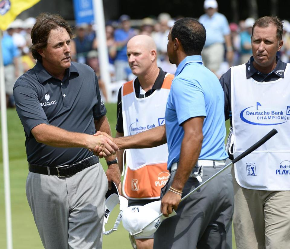 Phil Mickelson, who shot 63 to share the lead, shakes hands with Tiger Woods after they completed their first round. EPA/CJ GUNTHER