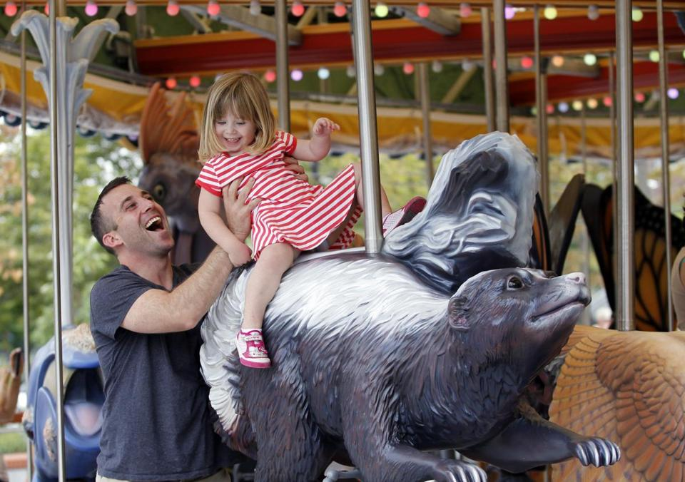 James Brunger helped his daughter, Stella, off the newly opened Rose F. Kennedy Greenway Carousel.