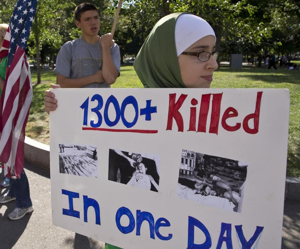Deema Alawa, 12, of East Hampstead, N.H., held a sign on Boston Common Sunday supporting US action against Syria's regime, a day after a protest against intervention.
