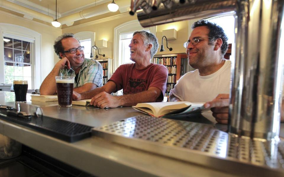 Owners of the Book & Bar John Petrovato, David Lovelace, and Jon Strymish at the bar with beer and books.