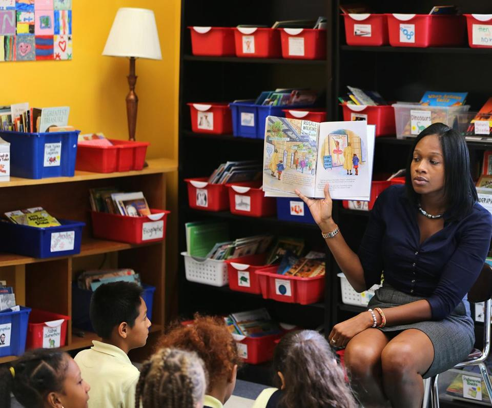 "Terese Clarke read ""Amazing Grace"" to a fourth-grade class at  Orchard Gardens K-8 pilot school during a visit by Governor Deval Patrick and other officials Wednesday. The school has emerged from the underperforming category."