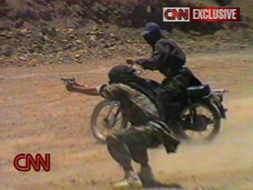 A man fired a weapon while another rode a motorcycle nearby in an excerpt released by CNN in 2002. CNN broadcast excerpts of videotapes that appeared to show al Qaeda members practicing assasination and kidnapping tactics.