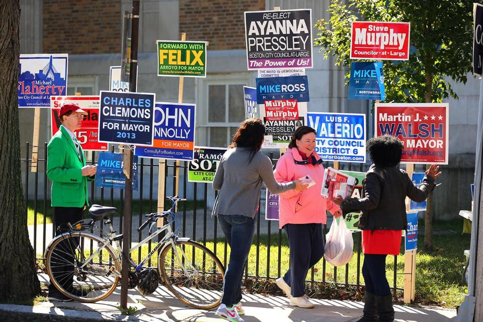 Campaign workers showed their support outside the Curley School in Jamaica Plain on Tuesday.