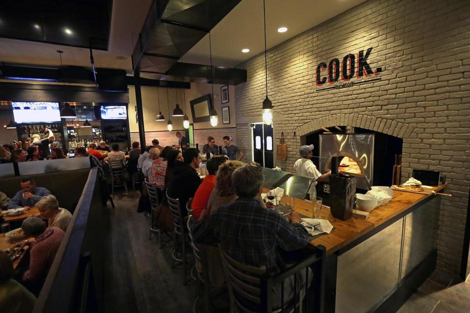 Cook is modern and casual, with gray-painted brick, wood floors, and metal chandeliers with dangling bulbs.