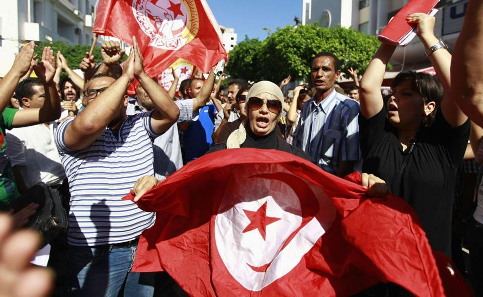 Anti-government protesters wave Tunisian flags as they called for the dissolution of the Islamist-led government this week.