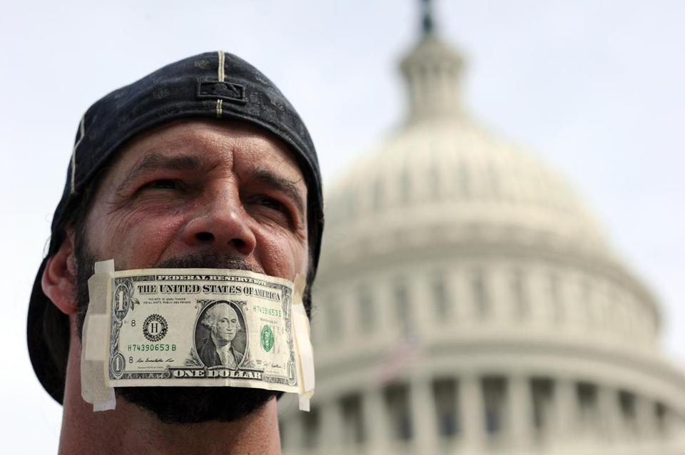 A protester's mouth was covered with a dollar bill during a demonstration in front of the US Capitol.
