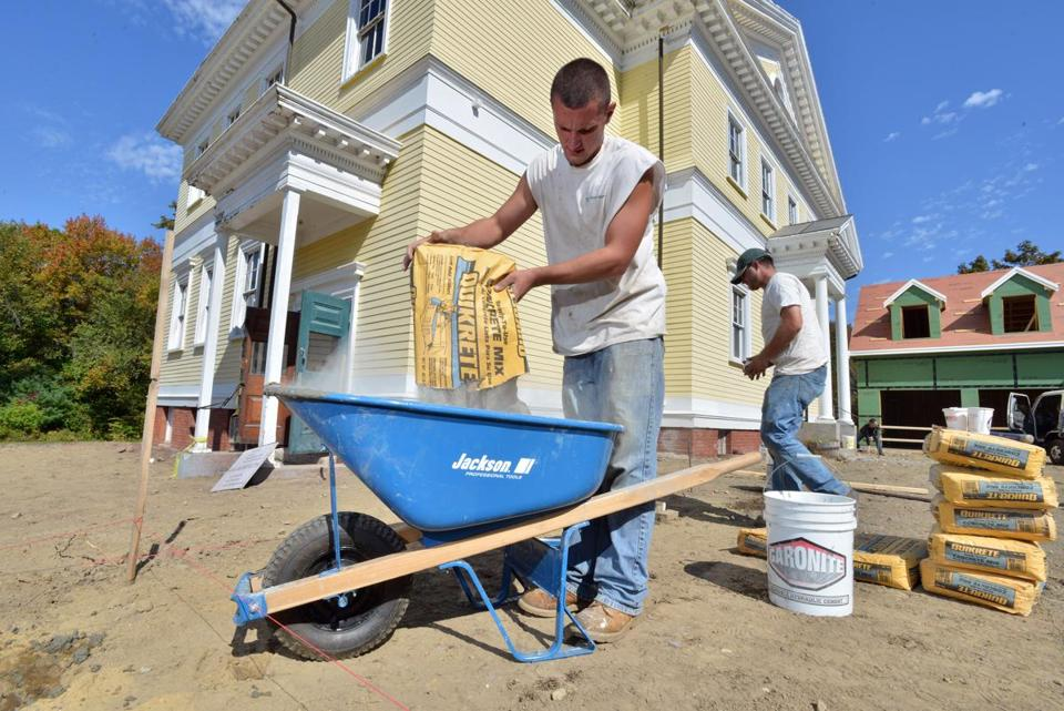 Carpenter Brett Labriola mixes cement for footings for a pergola in front of f the historic Yellow School House in Newbury which Local developer Chris Horan is the converting into a single family home.
