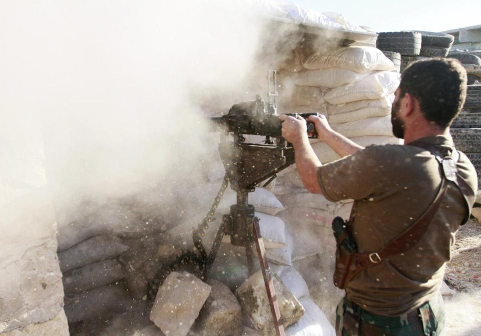A Syrian rebel fired Saturday toward the village of Aziza, which is under the control of government forces.