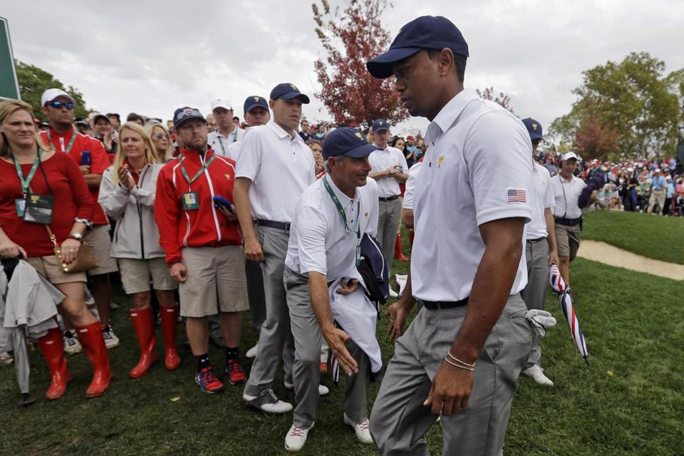 US captain Fred Couples greets Tiger Woods after he beat Richard Sterne to deliver the Americans' clinching point.
