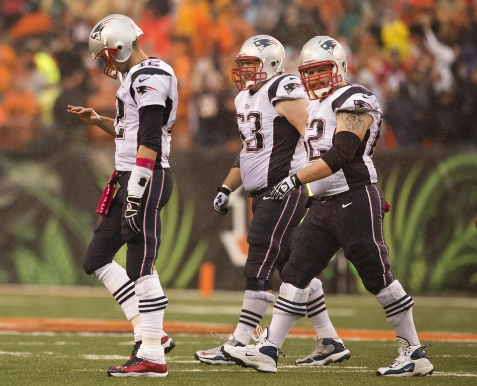 QB Tom Brady walks off the field looking at his throwing hand after tossing a late INT to the Bengals' Adam Jones.
