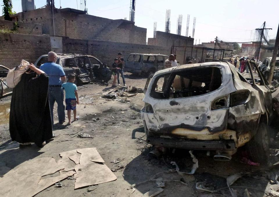 Iraqis inspect the site of bombing attack near a Shiite mosque in eastern Baghdad.