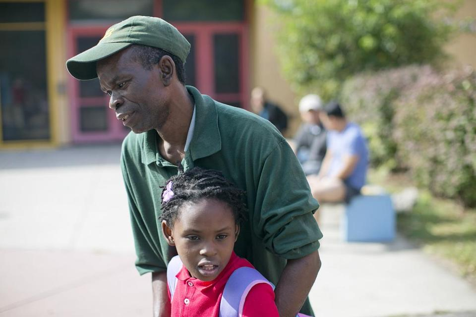 Odanese Cyriac held his daughter Vanessa, 7, as he spoke about picking her up from school Tuesday.