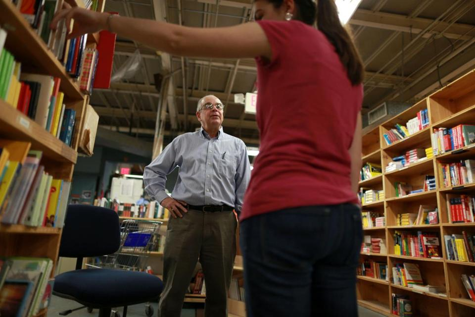 Tom Lyons, owner of New England Mobile Book Fair in Newton, talks to a customer in 2013.