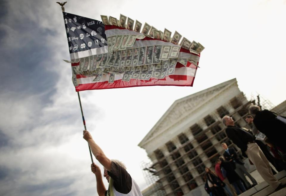 A protester waved a flag with corporate logos and fake money outside the Supreme Court.