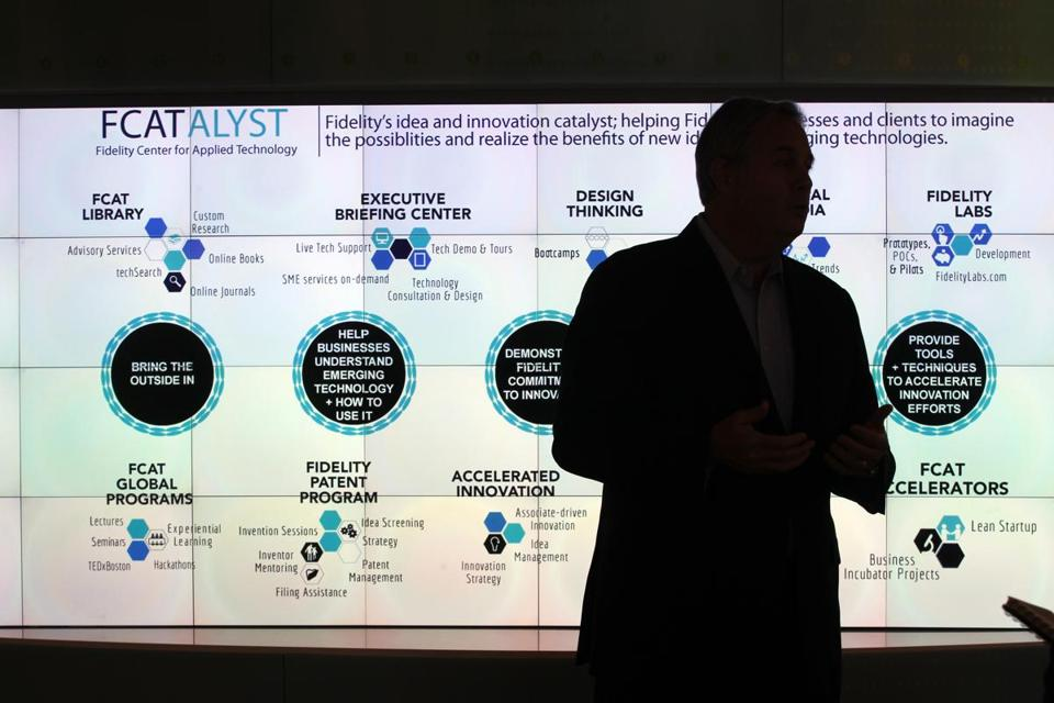 Sean Belka, director of the Fidelity Center for Applied Technology, is silhouetted against a global display at Fidelity Labs.