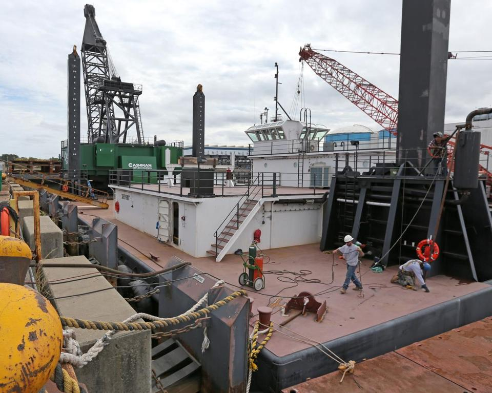 The 1,500-ton barge will set off from the Fore River Shipyard on Sunday, headed for dredging projects in Connecticut and Maine. It includes two giant clamshell bucket scoops (below).