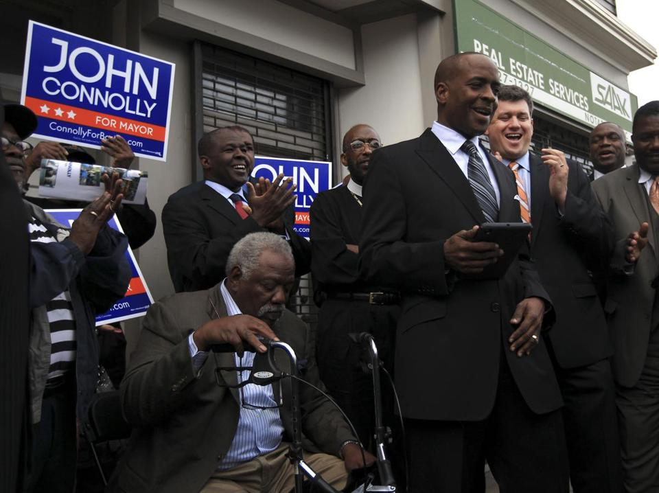 William Dickerson, pastor of the Greater Love Tabernacle Church (shown at right holding a tablet computer), led a gathering of black clergy members who endorsed John Connolly's bid for mayor in Roxbury on Thursday.
