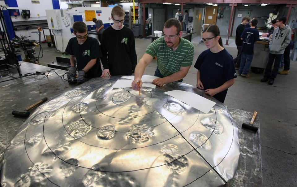 South Shore Regional Vocational Technical School instructor Bob Mello works with students (from left) Cal Hurley, Zach DeSouza , and Emma Sutcliffe on a 6-foot replica of the classic cookie treat.