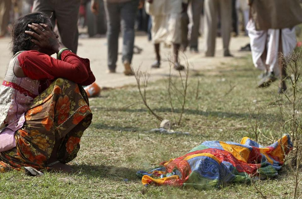 A woman cried next to the body of a victim. Many were believed to have drowned after jumping off a bridge into a river.