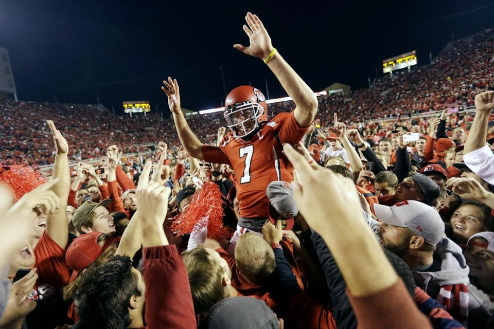 Utah quarterback Travis Wilson is hoisted by players and fans after the Utes stunned fifth-ranked Stanford in Salt Lake City.