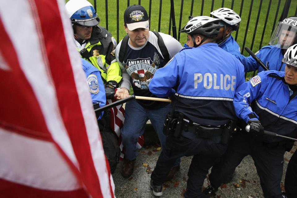 Law enforcement officers forced protesters down from the fence in front of the White House gates on Sunday.
