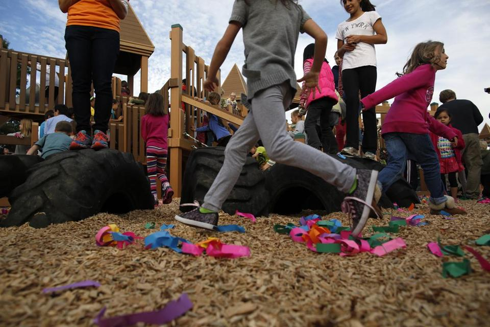 Children ran onto the playscape after breaking a paper chain which took the place of a ribbon cutting for the newly rebuilt Joey's Park in Belmont.