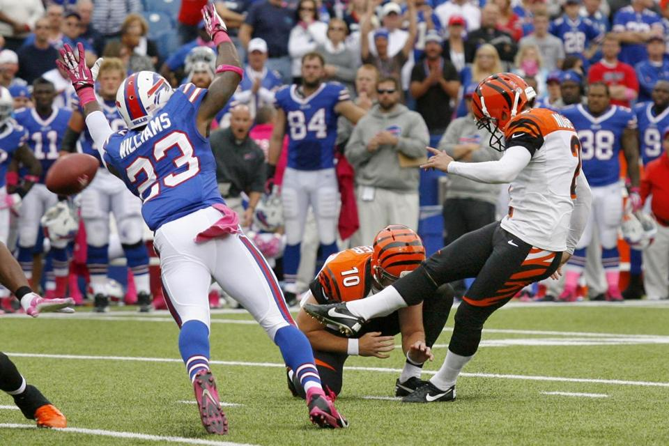 Mike Nugent sends the winning 43-yard kick on its way, past the Bills' Aaron Williams.