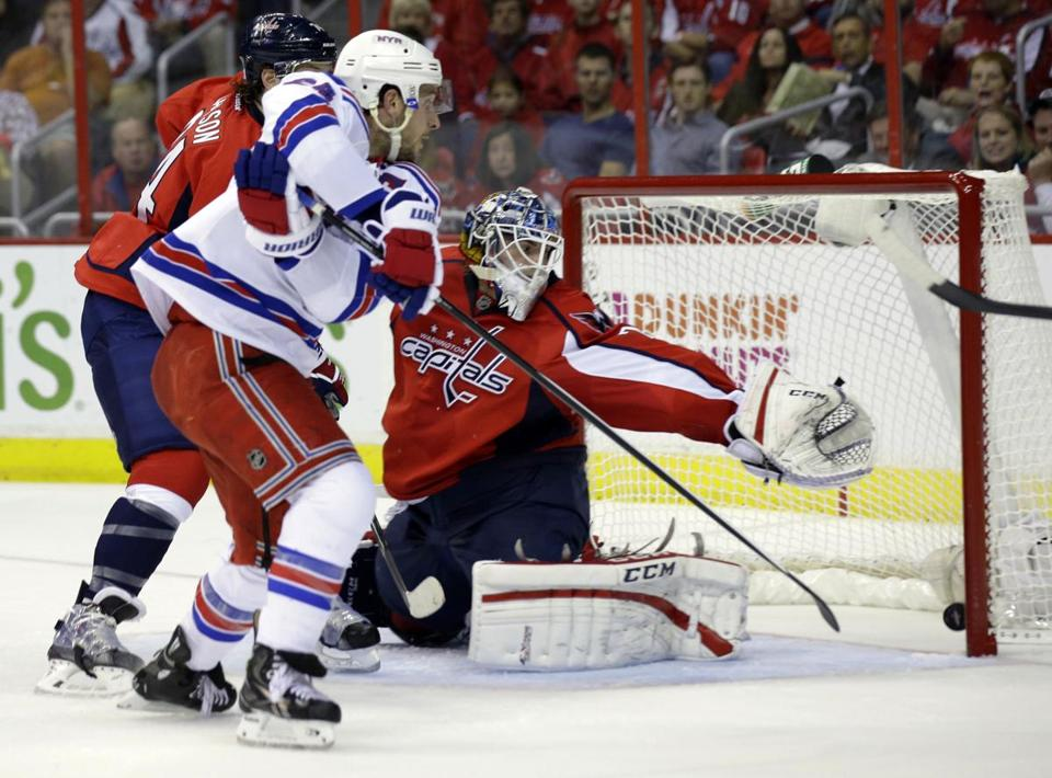 Rangers right wing Ryan Callaham (center) pushes the puck past Capitals goalie Braden Holtby to help New York stop a three-game slide.