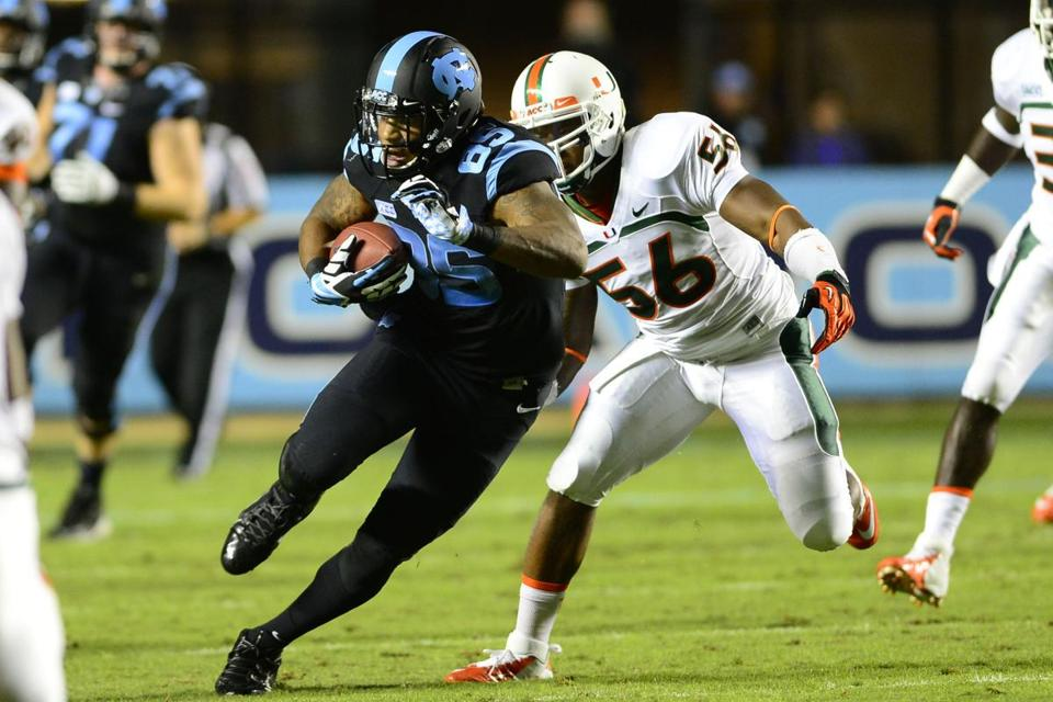 North Carolina tight end Eric Ebron is off on a 71-yard TD reception while Miami's Raphael Kirby pursues.