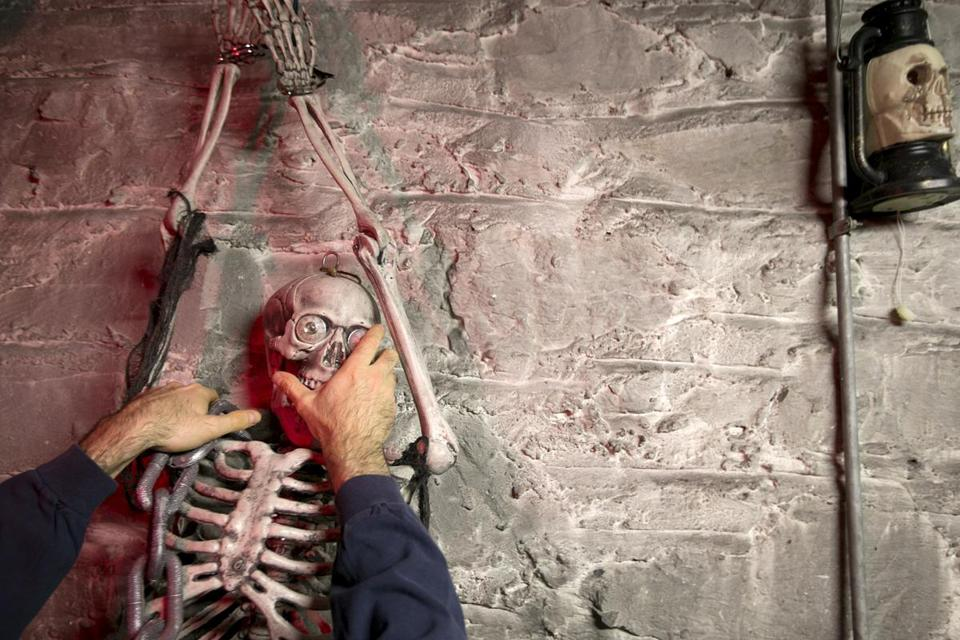 Dan Barrett adjusted a skeleton on a wall while setting up a room in the haunted house.