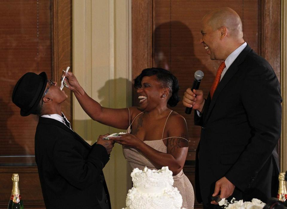 US Senator-elect Cory Booker (right) watched as Jenelle Torres feeds her spouse Lydia Torres a piece of cake after being married by Booker in Newark, N.J., early Monday.
